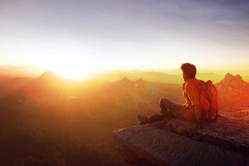 man sitting on edge facing sunset 915972